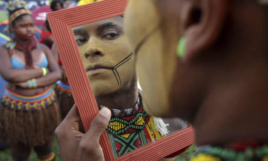 A young indigenous man applies body paint in Brasília.