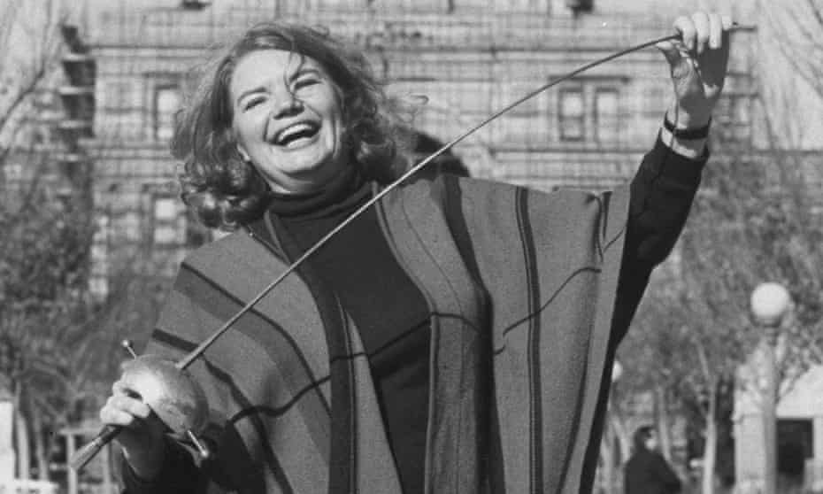 Molly Ivins, known for her rapier wit, poses with a fencing sword in front of the Texas state capitol in Austin.
