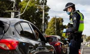 Police officers check reasons for not being at home at a random checkpoint  in Broadmeadows