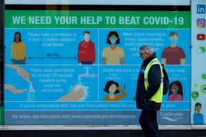 People passing by a sign asking for help to beat Covid-19 in Halifax, West Yorkshire.
