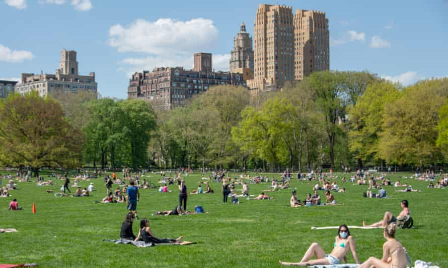 People gather in New York's Central Park – some masked, others not.