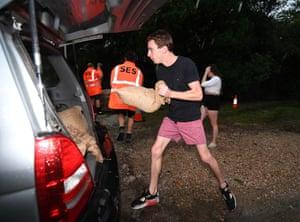 A man loads sandbags into his car in Murwillumbah, NSW