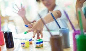 Preschool children fingerpaint in class.