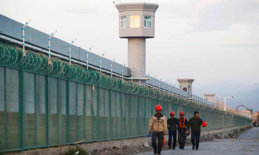 Workers walk by the perimeter of a 'vocational skills education center' in Xinjiang, China.