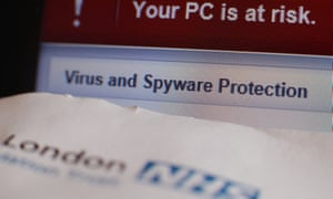 A patient appointment letter from a London NHS hospital, next to a virus and spyware warning message on a laptop screen at a home in London,