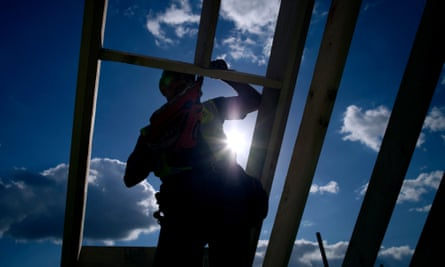 A builder on the roof of a new house at a development by Persimmon