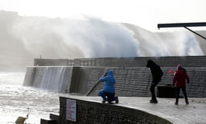 People watch waves crashing against the seafront in Auderville, Normandy, as storm Eleanor hits the northern part of France