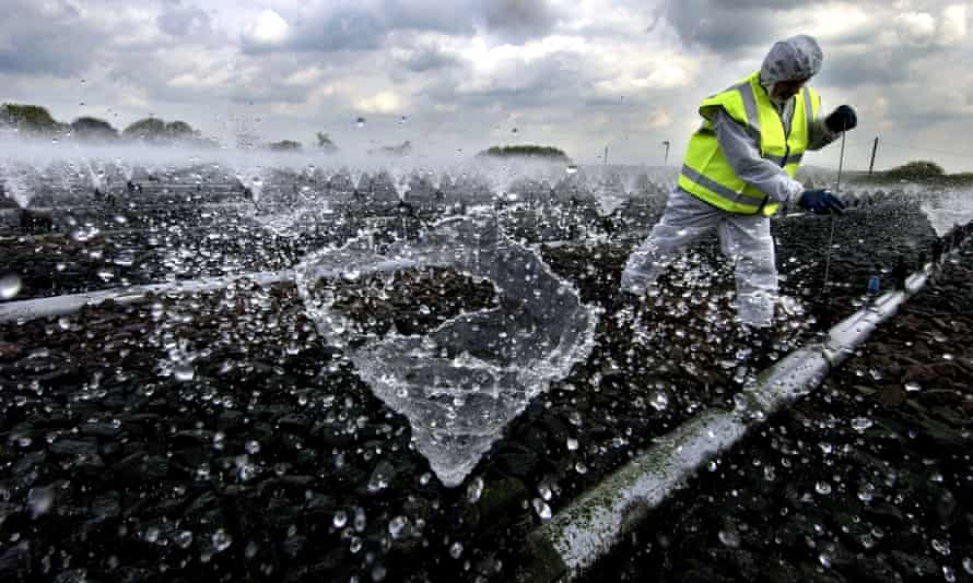 A worker carries out cleaning and maintenance work at a sewage works