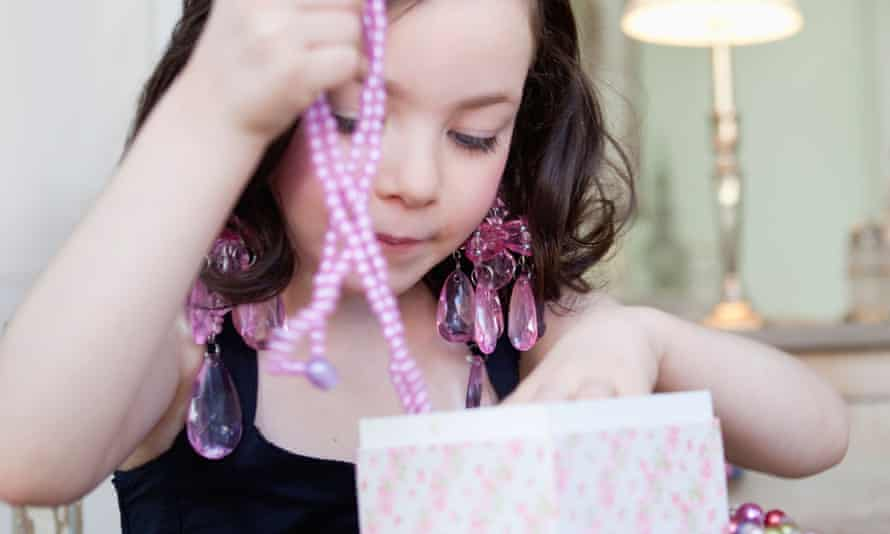 Young girl takes a bright pink necklace from a jewellery box