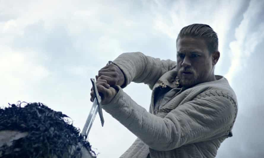 charlie hunnam as king arthur pulling excalibur from the stone