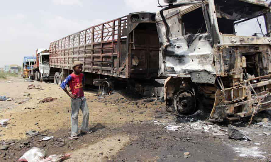 A Yemeni boy stands next to burnt trucks following a reported airstrike by the Saudi-led coalition in the Hays District of the province of Hodeidah.