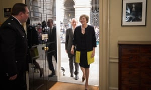 Theresa May, followed by her husband Philip John, walks into 10 Downing Street.