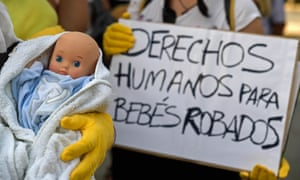Demonstrators hold a baby doll and placard reading 'Human rights for stolen babies' outside a court in Madrid'.