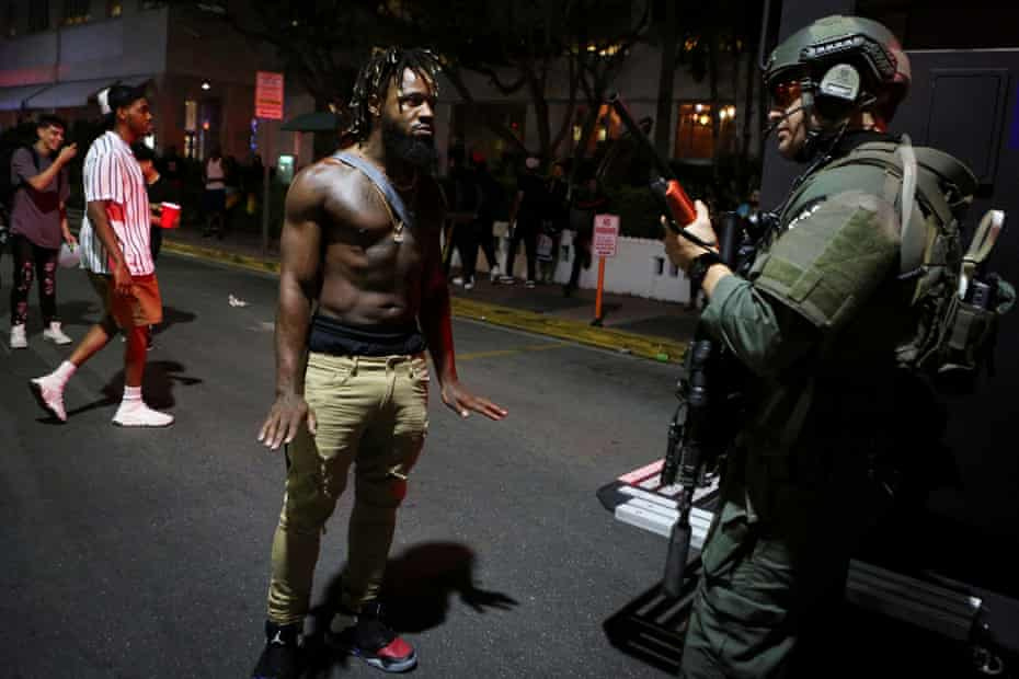 A man talks to a police officer as revelers enjoy spring break festivities despite an 8pm curfew in Miami Beach, Florida.
