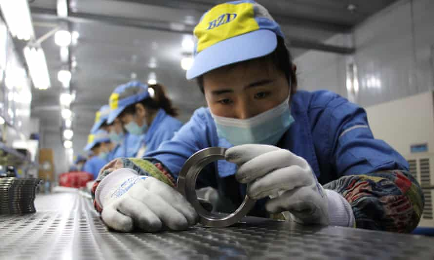 Workers checking aluminium pistons for vehicle engines at a factory in Binzhou, in China's Shandong province