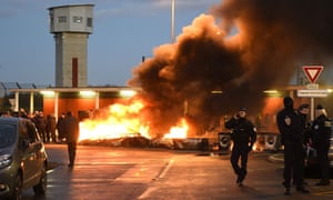 Police stand near striking prison guards and burning wooden palettes at the Vendin-le-Vieil jail