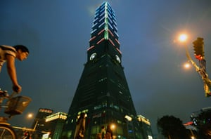 In Taipei, a man rides next to the 101 building lit up with the colours of the French flag in honour of the victims.
