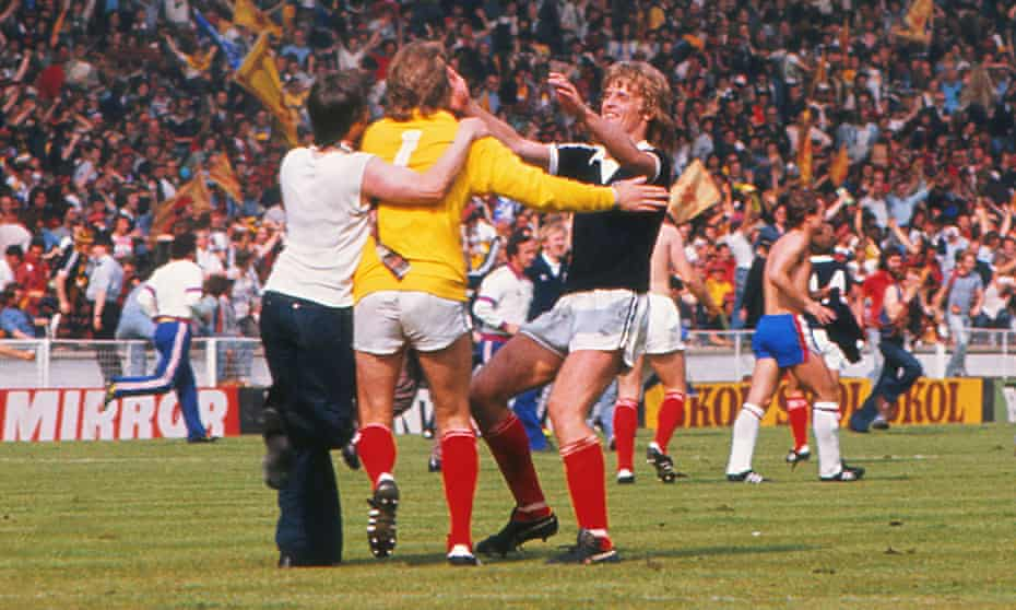 A Scotland fan celebrates on the pitch with Alan Rough and Gordon McQueen at Wembley in 1977