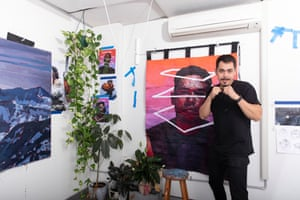 Abdullah in boxing stance in front of his paintings