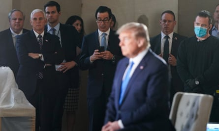 Vice-President Mike Pence and the treasury secretary, Steven Mnuchin, with phone, watch as Donald Trump participates in a live Fox News virtual town hall called 'America Together: Returning to Work'.