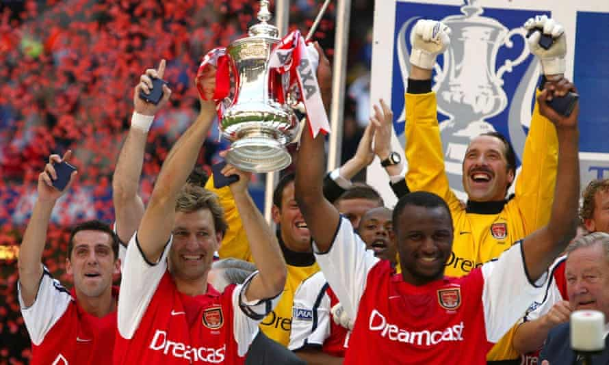Adams and Patrick Vieira lift the FA Cup for Arsenal after victory over Chelsea in 2002. It was Adams' 669th and last game for the Gunners.