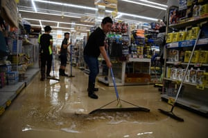 Workers clear floodwater from a store in Kurume, in Fukuoka prefecture