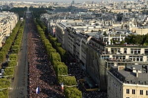 Supporters gather on the Champs-Elysees avenue in Paris as they wait for the arrival of the French national football team for celebrations
