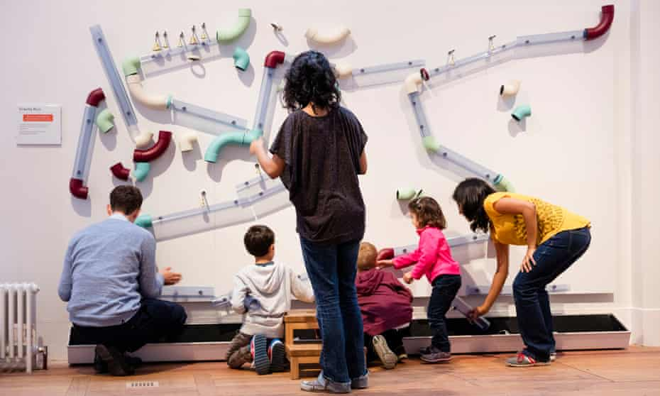 Adults and children experiment with the Gravity Run at Wonderlab in London's Science museum.