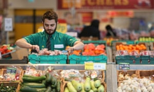 An employee works on the fresh vegetable display at a Morrisons supermarket