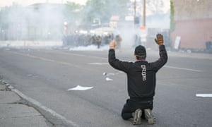 A man takes a knee near the fifth precinct police station during the George Floyd protests on Saturday, 30 May 2020, in Minneapolis, Minnesota.