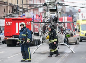 Firefighters, emergency service vehicles and a helicopter near the metro station