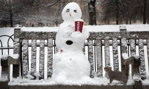 A snowman with a cigarette and coffee cup is viewed by a squirrel in St James's Park, London