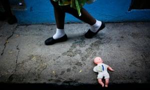 Child walks past doll on ground.