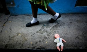 A child walks next a doll at orphanage