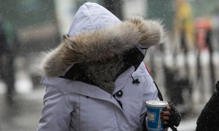 A woman walks through a snowstorm in New York City. Temperatures are dropping and down-lined coats will be in ever greater demand.