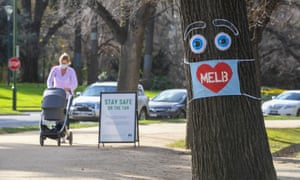 A woman pushes a pram past a large face mask pinned to a tree in Melbourne on 3 August 2020.