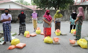 Rohingya refugees wearing protective masks practise distancing while waiting to receive goods from volunteers in Kuala Lumpur, Malaysia, on 7 April