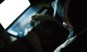 A hooded man typing into a laptop