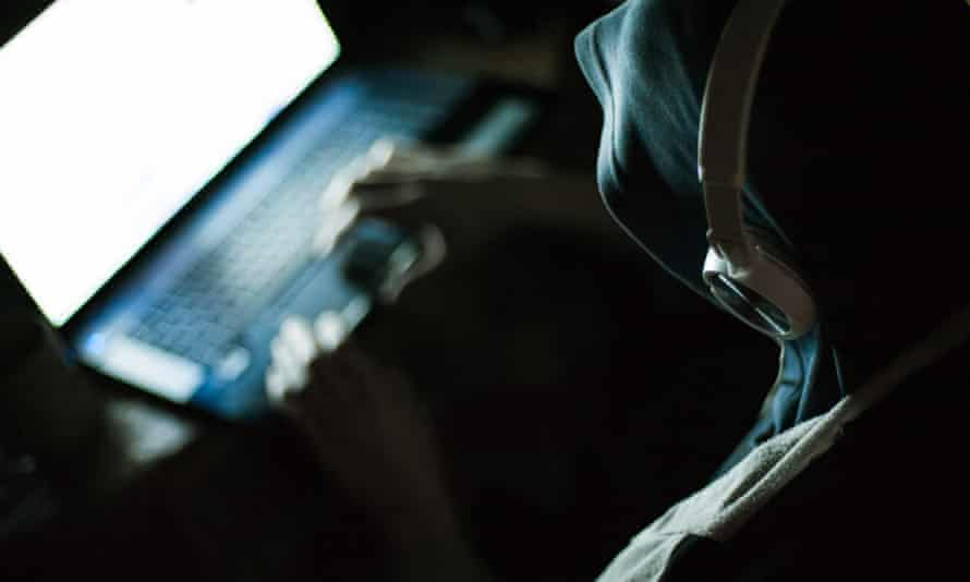 Computer hacker working on laptop in the dark