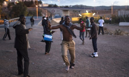 A migrant runs towards the temporary holding centre (CETI) after scaling Melilla's border fence with Morocco.