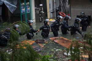 Police officers form a chain on a flooded street during a rescue operation in Lei Yue Mun, Hong Kong