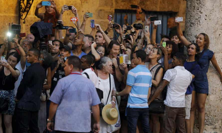 Tourists and local residents take pictures of President Barack Obama as he tours Old Havana.