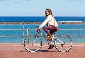 A girl rides her bike on the promenade of Las Canteras Beach, Gran Canaria