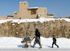 Kabul, Afghanistan. A man wheels a TV on a snow-covered street