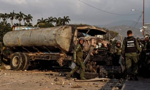 Members of the Venezuelan national guard next to a burnt truck on the border with Colombia