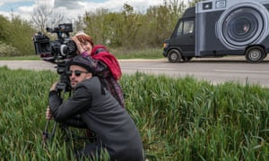 Still from Faces Places, showing the two directors and stars with a camera in a field.