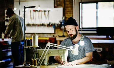 Man sewing canvas bag on industrial sewing machine.