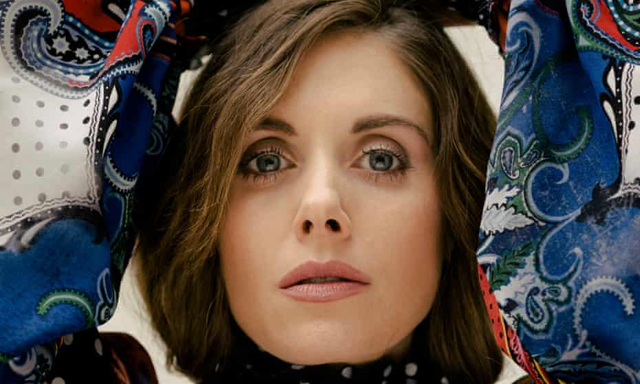 Close-up of the face of Alison Brie, her hands above her head, the puffy sleeves of her patterned top either side of her face