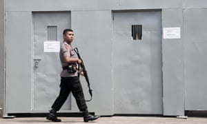 An Indonesian police officer guards the gate to Indonesia's highest security Nusa Kambangan prison, where those facing imminent execution are held.