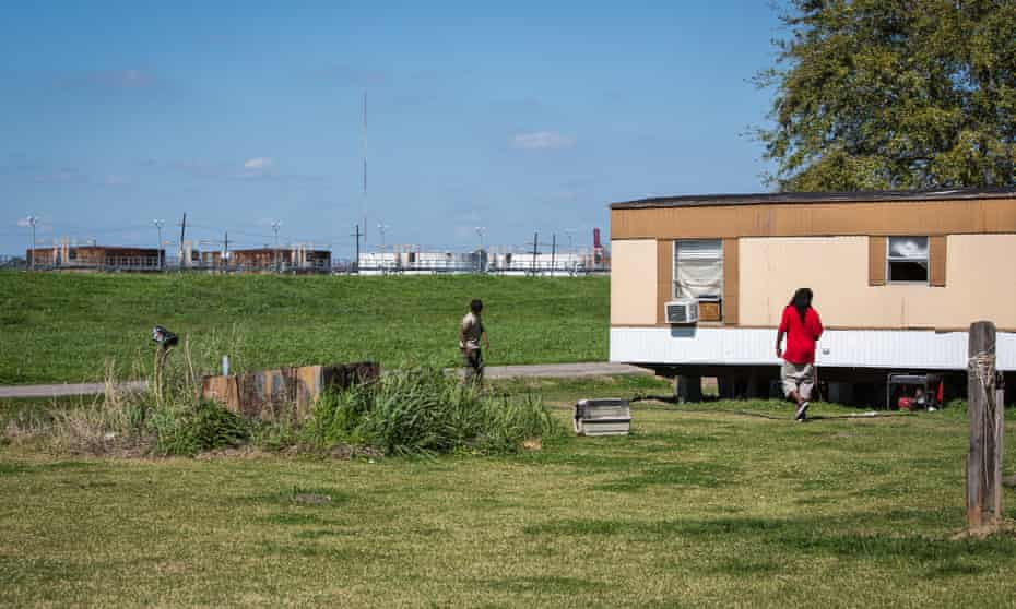 Mobile home in St James Parish with oil tanks in the background. The rise of the oil and petrochemical industry at their doorstep has thrust residents into a financial trap.